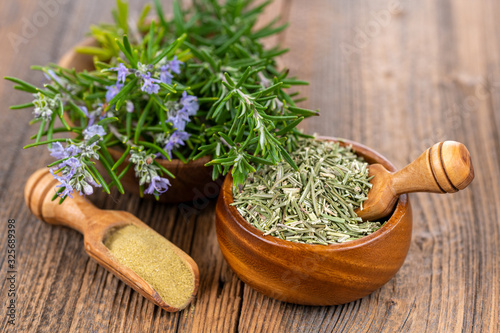 Obraz na płótnie A wooden bowl with blooming and fresh rosemary twigs, a wooden bowl with whole d