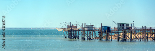 Photo Typical old wooden fishing huts on stilts in the atlantic ocean near La Rochelle