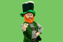 Pointing, Choosing. Excited Leprechaun In Green Suit With Red Beard On Green Background. Funny Portrait Of Man Ready For Sales. Saint Patrick Day, Human Emotions, Celebration, Traditional Holidays.