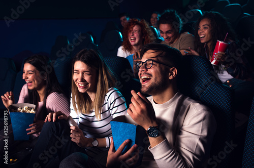Fototapeta Group of cheerful people laughing while watching movie in cinema. obraz