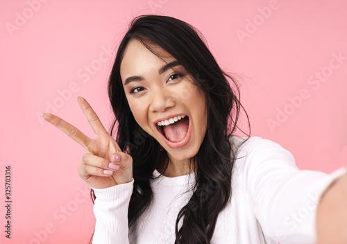 Obraz Cheerful pretty young asian woman taking a selfie - fototapety do salonu