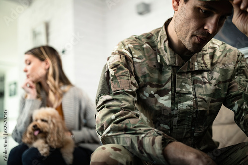 Fotografiet Young sad military officer with his wife at home.