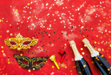 Two Champagne Bottles, Carnival Mask, Tongue Pipe And Confetti On Red Background. Flat Lay Of Purim Carnival Celebration Concept.