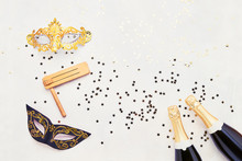 Two Champagne Bottles, Carnival Mask And Gragger On Light Background. Flat Lay Of Purim Carnival Celebration Concept. Top View, Copy Space