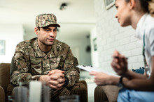 Young Pensive Military Man Having Counselling With A Nurse At Home.