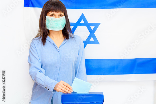 Fotografie, Tablou Israeli woman with face medical protected mask putting ballot in a ballot box on election day on Israel flag background