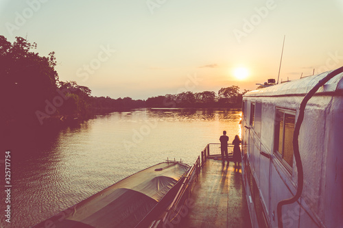 Amazon rainforest sunset during a boat trip with a reflection of the trees in the water Canvas Print