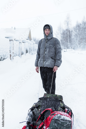 Adult Caucasian man walking with drag sled in the snowy village during strong sn Tableau sur Toile