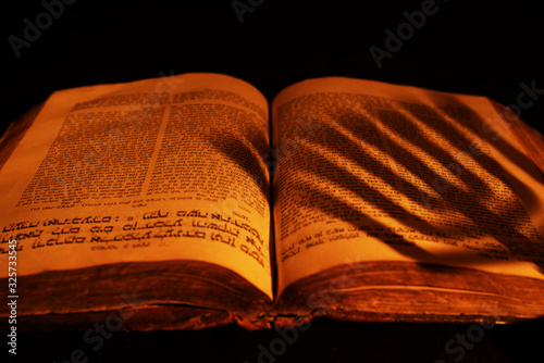 Photo Old Hebrew Bible in light of burning candle on dark background