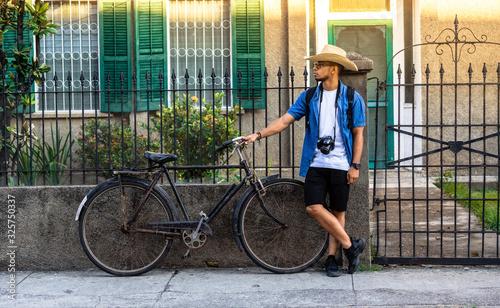 Photo retrato completo de hombre hispano usando un sombrero, una camisa de botones color azul con una camara colgando de su cuello,  sosteniendo una bicicleta, parado en una calle