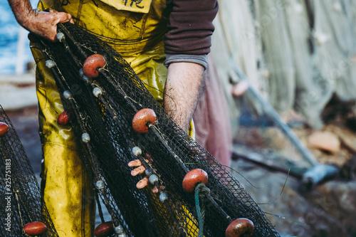 Canvas Print Mains d'un pêcheur en train de ranger ses filets de pêche