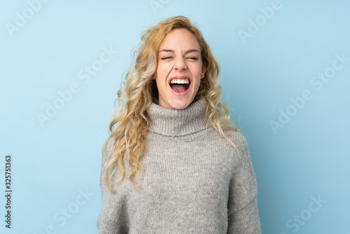 Fototapeta Young blonde woman wearing a sweater isolated on blue background shouting to the