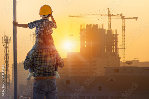 Obraz Asian boy on father's shoulders with background of new high buildings and silhouette construction cranes of evening sunset, father and son concept - fototapety do salonu