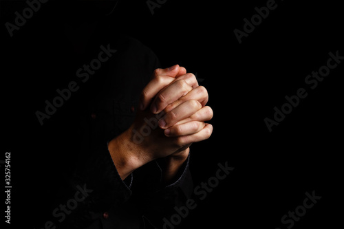Fotomural Image of praying hands on a black background