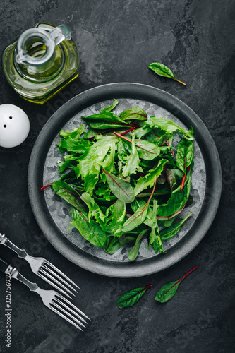 Fotografia Mix fresh green leaves of lettuce for salad on a dark stone background