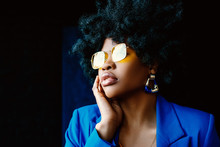 African American Fashionable Woman Wearing Trendy Yellow Sunglasses, Blue Earrings, Classic Blazer. Young Beautiful Model Posing On Dark Background. Close Up Portrait. Copy, Empty Space For Text