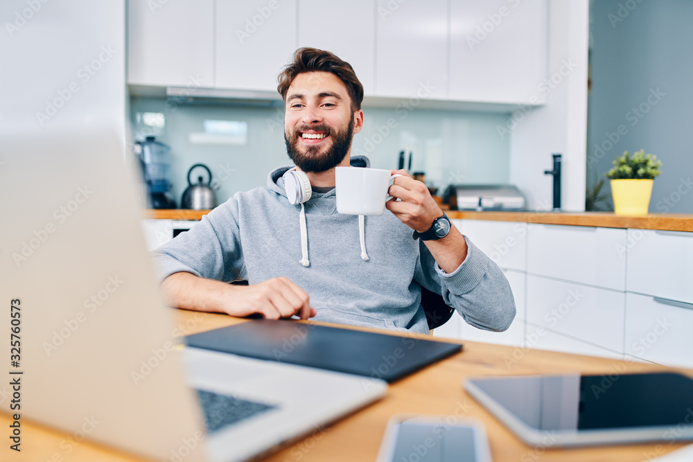 Fototapeta Joyful young web developer drinking coffee while taking break from work in home office