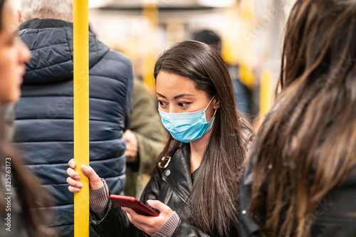 Fotografering Chinese woman wearing face mask in the train