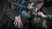Woman Reaching For Handgun To Defend Against Attacker. Women's Personal Defense And Concealed Carry Concept