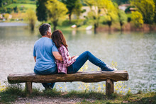 Young Couple Sitting On Bench Under A Tree At Lake In Italy.