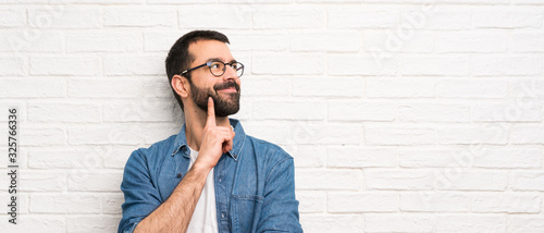 Fototapeta Handsome man with beard over white brick wall thinking an idea while looking up obraz
