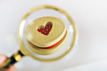 A Red Heart In A Wooden Round Box Is Held By A Man's Hand