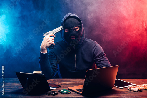 Fototapety, obrazy: hacker man in pullover going commit suicide, he brought barrel of gun temple, preparing shoot. hacker after failure of getting access to data, going to kill himself. cyberattack concept