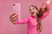 Funny Young Redhead Woman Making Selfie. Smiling Girl Wearing Pink Blouse Holding Pink Smartphone, Making Faces On Camera, Posing For Selfie Isolated On Pink Background.