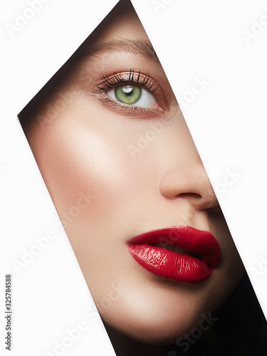 young beautiful woman with makeup into hole of white paper Wall mural