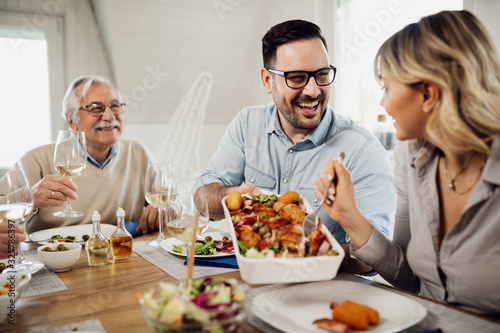 Happy man passing food to his wife during family lunch at dining table Fototapet