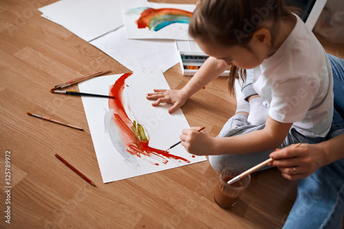 Obraz creative present for granny. woman and her kid paintiong a rainbow, art close up side view photo - fototapety do salonu