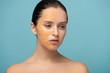 attractive girl applying yellow sugar exfoliant on face, isolated on blue