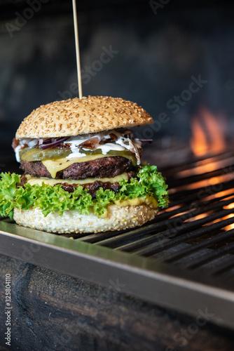 Duży burger ze świeżymi warzywami i serem owinięty w papier ekologiczny. Grillowana kanapka meksykańska na drewnianym stole w stylu industrialnym. Hamburger na wynos z widokiem na ogród.