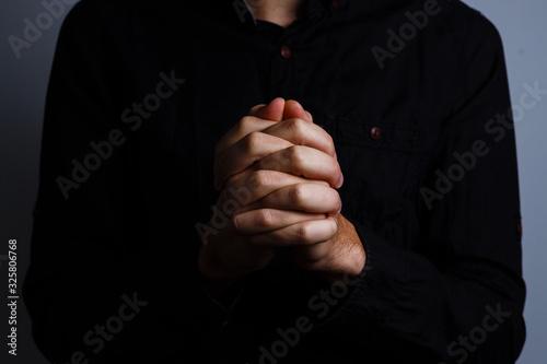Fényképezés Image of praying hands on a black background