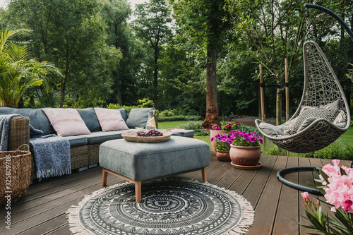 Garden patio decorated with Scandinavian wicker sofa and coffee table Fototapete