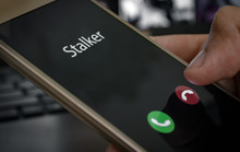 Stalker Caller. A Man Holds A Phone In His Hand And Thinks To End The Call. Incoming From An Unknown Number At Work. Incognito Or Anonymous, Scammer Or Stranger