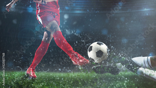 Fotografija Football scene at night match with player in a red uniform kicking the ball and