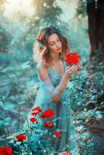 Princess Enjoy Sunny Nature, Silence Harmony Eyes Closed, Holds Touch Red Rose. Hairstyle Decorated Leaves, Loose Hair. Fairy In Long Sexy Airy Blue Dress With Lace. Backdrop Summer Forest Trees, Bush