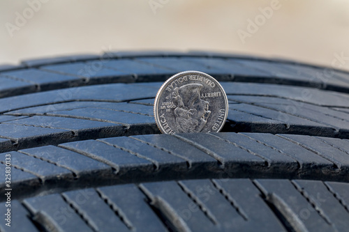 Fototapeta Closeup of checking tire tread wear depth of old tire using a quarter coin. Concept of automobile safety, maintenance, and repair obraz