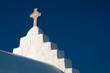 Stone Cross Standing On Rough White Stucco Steeple Of Traditional Greek Island Church Under Bright Blue Mediterranean Sky
