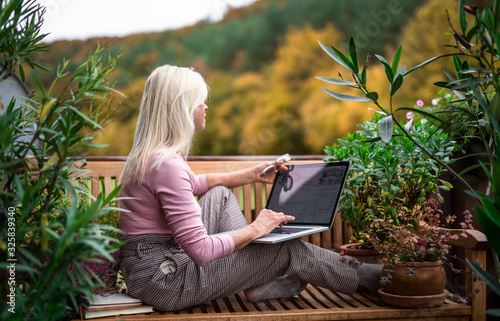 Fotografiet Senior woman architect with laptop sitting outdoors on terrace, working