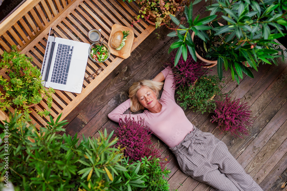 Fototapeta Top view of senior woman with laptop lying outdoors on terrace, resting.