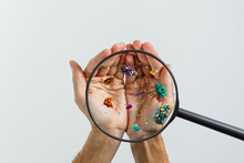 Close Up On A Sick Man Hand Through Magnifying Glass Transmitting Virus By Skin Contact 3D Rendering