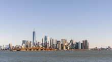 Daytime Photo Of Lower Manhattan New York City Skyline Across The Hudson River With Ellis Island In The Foreground. Clear Blue Sky. Room For Text..