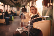 Young Woman Looking At Camera While Traveling In Subway Train
