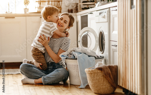 Cuadros en Lienzo happy family mother housewife and child   in laundry with washing machine