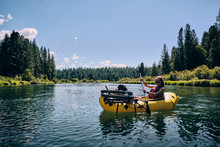 Woman Paddles On The Deschutes River In A Pack Raft In Oregon.