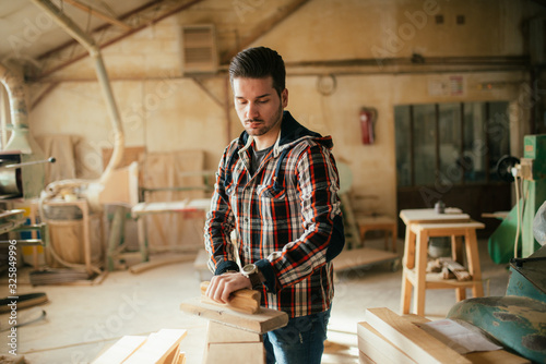 Young handsome carpenter flattening wood - 325849996