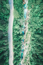 Aerial Of A Highway Through Forest Next To Teal Blue River