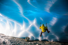 Mountaineer Ice Climbing On Glacial Ice In Ice Cave.